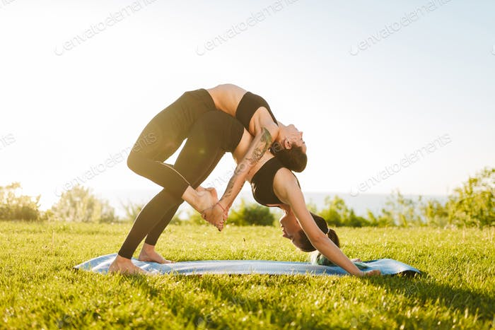 Two beautiful ladies in black sporty tops and leggings training yoga poses together outdoors