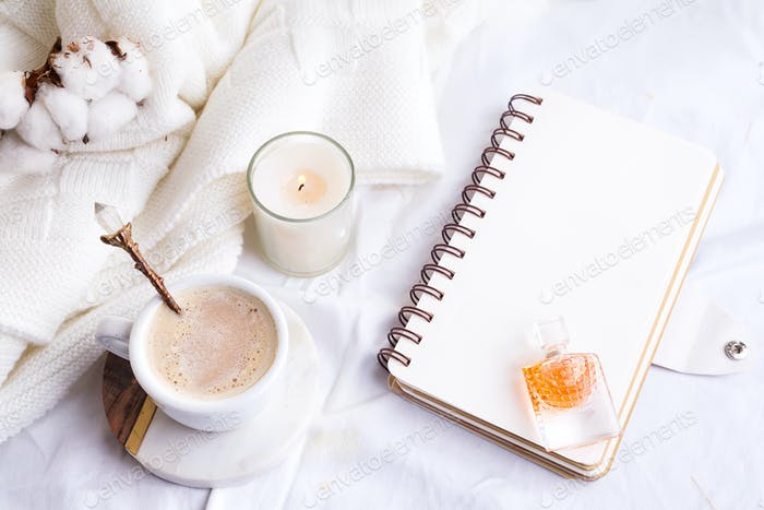 Morning coffee mug with notebook, candle and cotton flowers on a white bed top view . Woman cozy