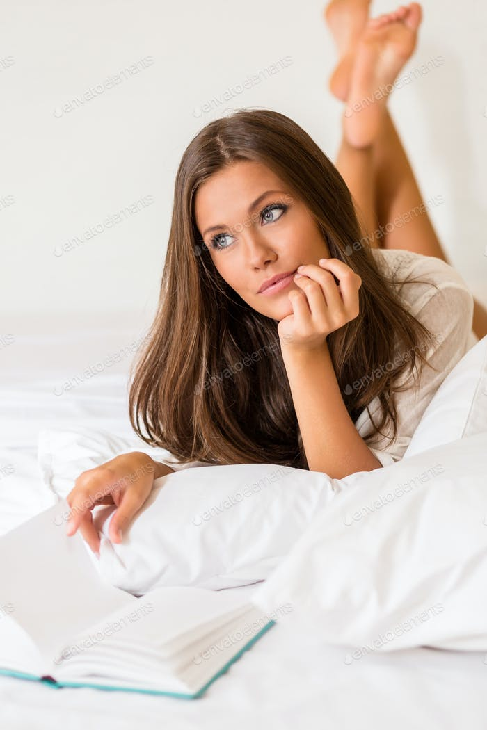 Young woman read book in bed.