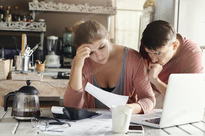 Young married couple facing financial problem during economic crisis. Frustrated woman and unhappy m