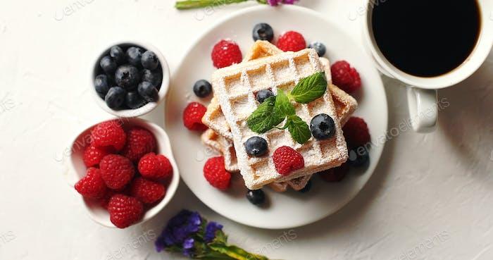 Coffee and berries near waffles