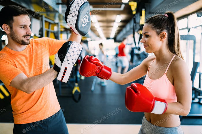 Picture of woman wearing boxing gloves and her trainer