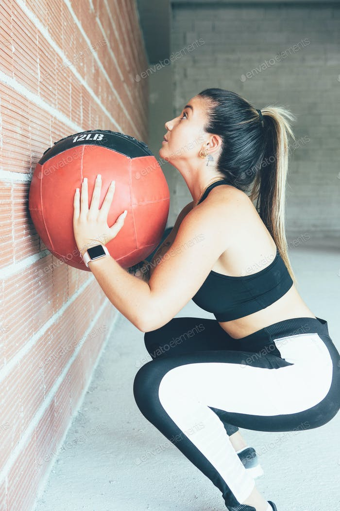 Concentrated_fit_woman_does_wall_ball_routine