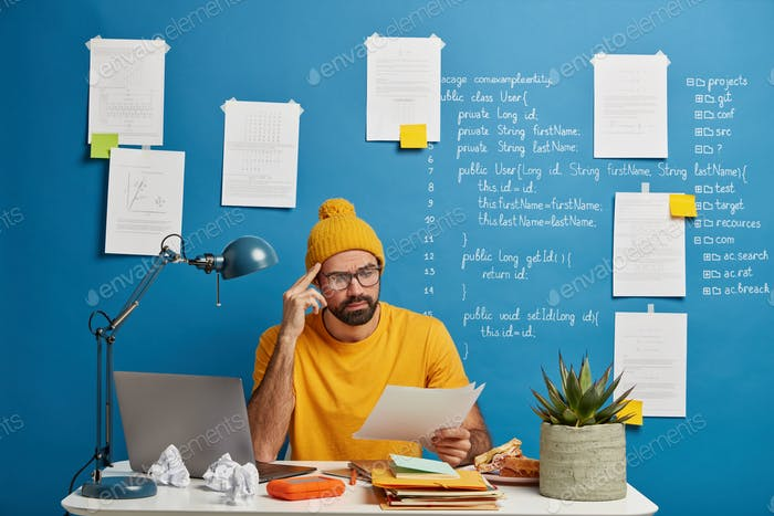 Serious male employee or freelancer considers paper document, wears yellow hat and t shirt, studies