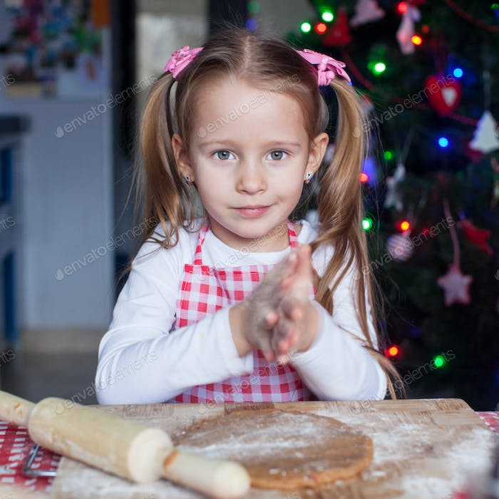 Adorable little girl baking gingerbread cookies for Christmas
