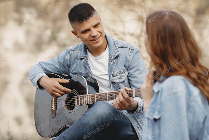Junges Paar verliebt in eine Karriere mit einer Gitarre