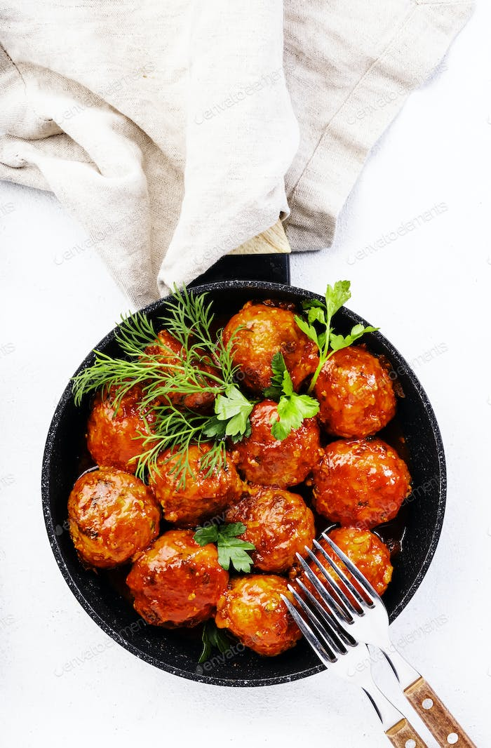 Meatballs with tomato sauce and spices in frying pan on white kitchen table