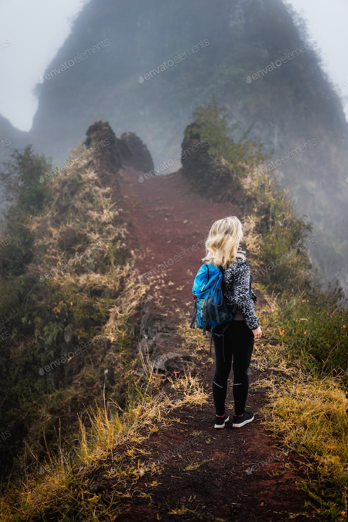 Woman hiker with backpack on the narrow misty path of mountain ridge on Santo Antao island, Cape