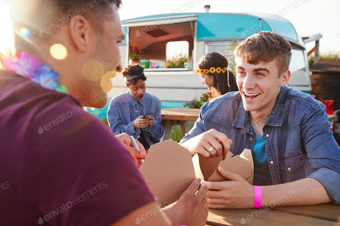 Group Of Friends Eating Takeaway Food From Truck At  Outdoor Music Festival