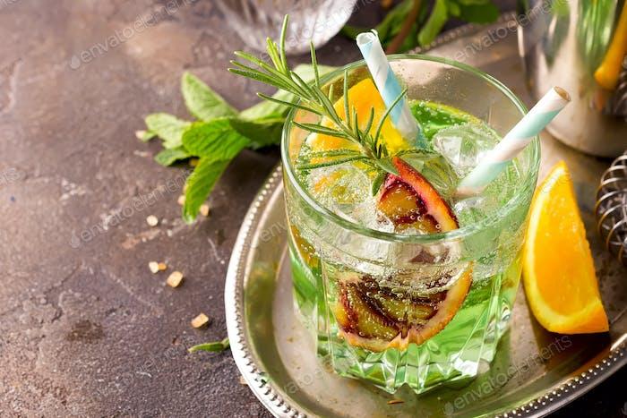 Süßer erfrischender Minzlikör, mit Eis, roter Mandarine und Rosmarin auf dem Metalltablett, um sich von Grau zu ernähren