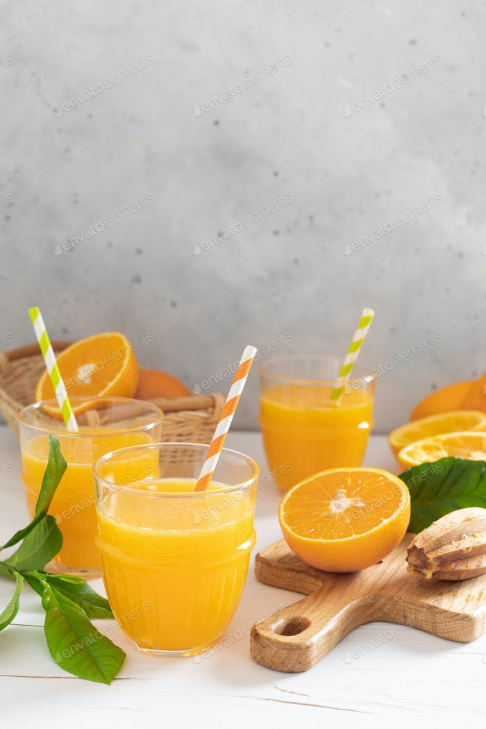 Orange juice. Freshly squeezed juice in glasses and fresh fruits with leaves