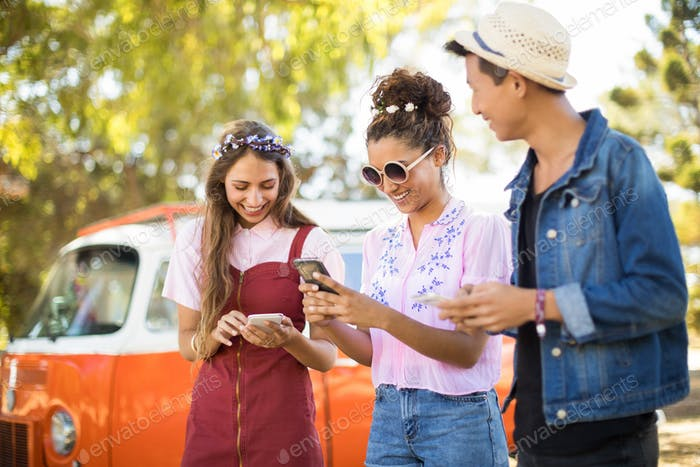 Smiling friends using phone while standing on field