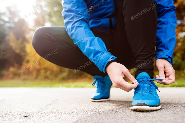 Unrecognizable runner crouching, tying shoelaces, close up