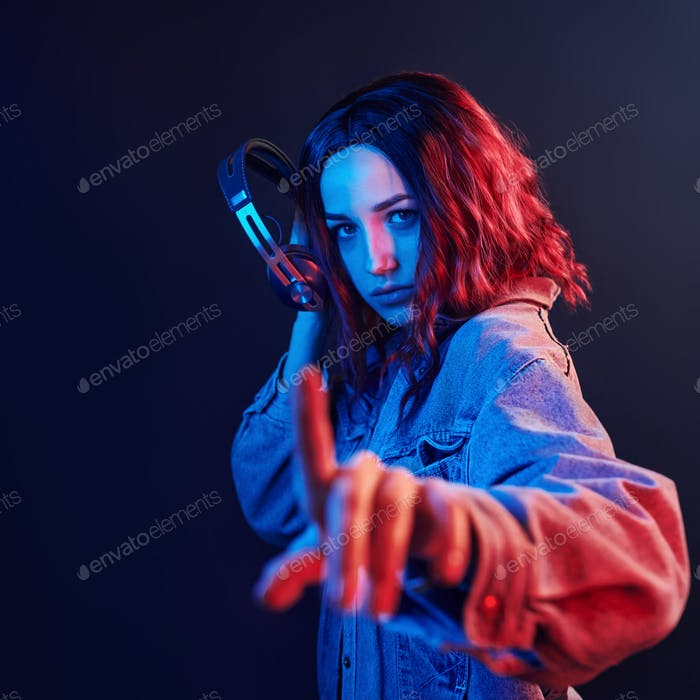 Portrait of young girl that listening to music in headphones in red and blue neon in studio