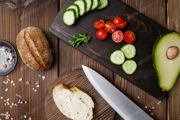 Cutted tomatoes and cucumbers, wooden background