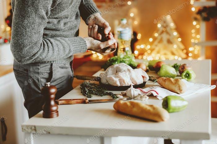 Junger Mann kochen Huhn für Weihnachten