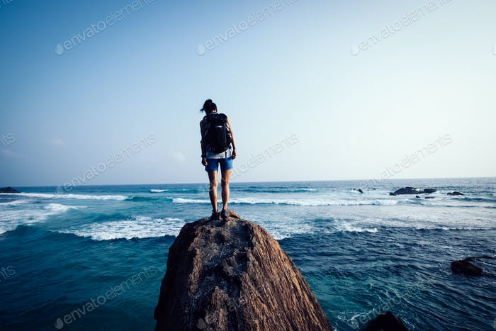 Young woman on seaside rock cliff edge looking down
