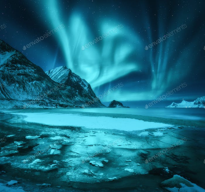 Northern lights over snowy mountains, frozen sea coast