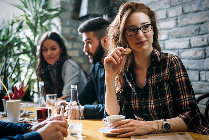Woman eating cookies and drinking coffee in restaurant