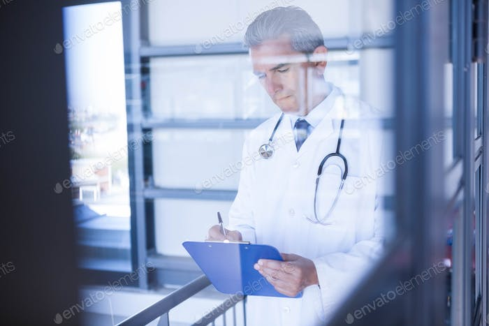Male doctor writing on clipboard in hospital