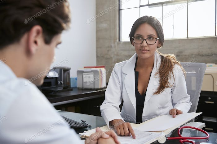 Concerned female therapist counselling young male patient