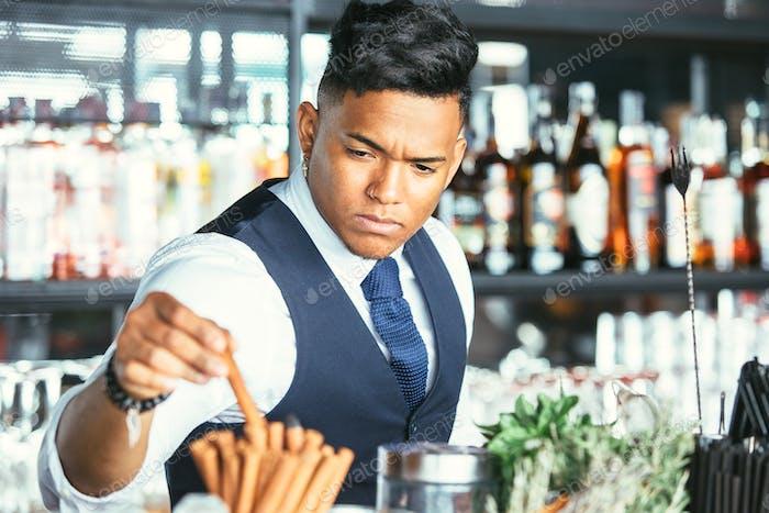 Expert barman taking cinnamon stick