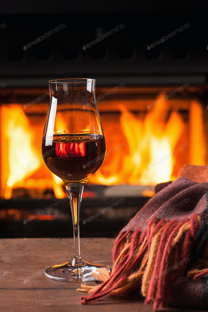 glass of cognac in front of fireplace