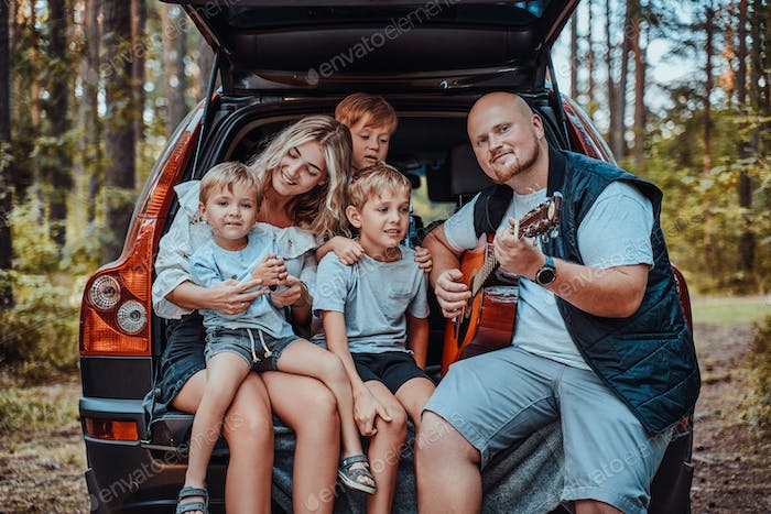 American family with their car on weekend in wood