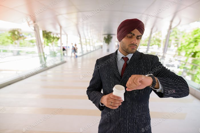 Indian Sikh businessman checking smart watch and holding coffee