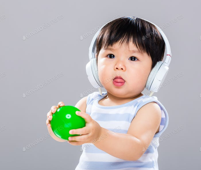 Asian baby boy wear with headphone and play with green ball