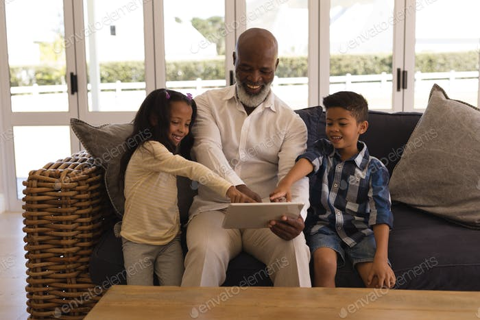 Family using digital tablet in living room at home