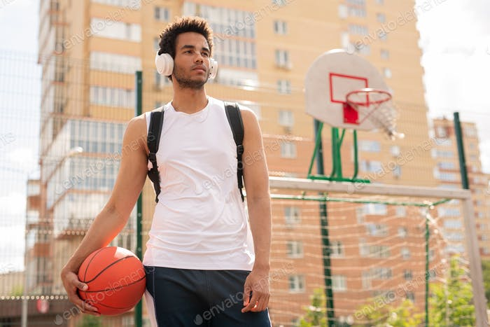 Sportive guy with ball for playing basketball listening to music in headphones