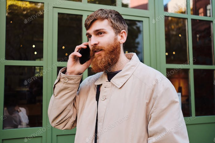 Young handsome bearded man dreamily looking away talking on cellphone