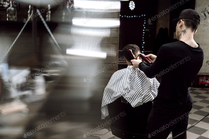 Men's style. The fashion barber makes a stylish hairstyle for a black-haired man sitting in the