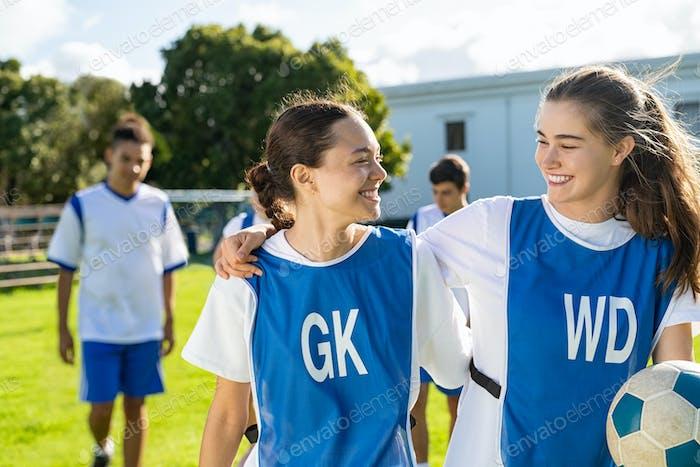 Girls in sport uniform celebrating football game victory