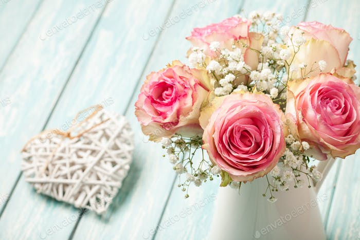 Pink roses in jug and heart decoration on blue background