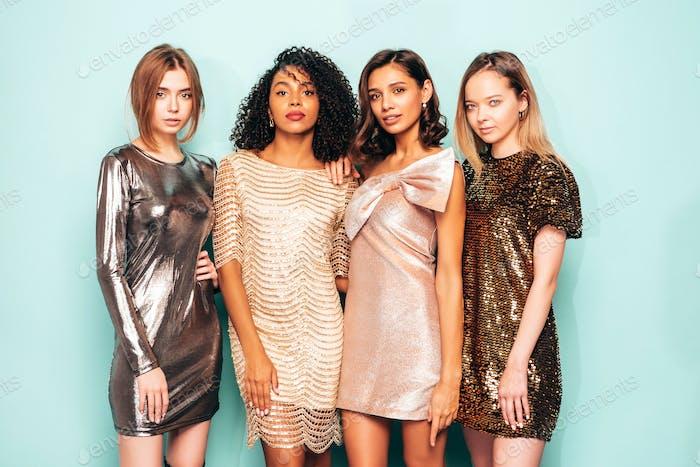 Portrait of four young beautiful women in dresses posing in studio