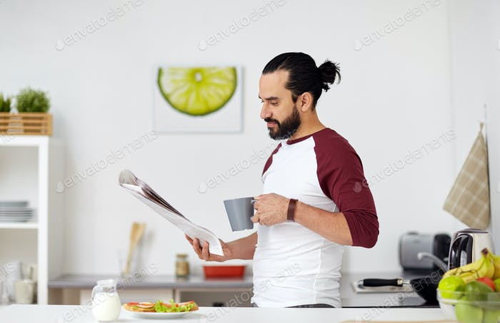 man reading newspaper and eating at home kitchen