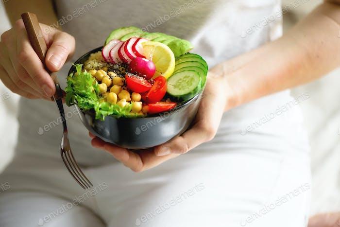 Mädchen in weißer Jeans hält in den Händen Gabel, veganes Frühstück Mahlzeit in Schüssel mit Avocado, Quinoa, Gurke