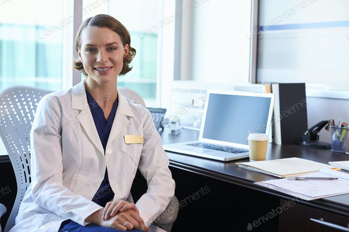 Portrait Of Female Doctor Wearing White Coat In Office