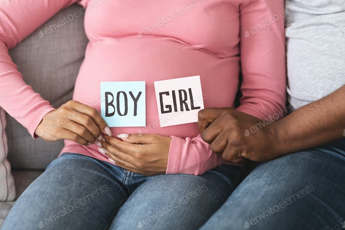 Expecting couple holding color cards for baby boy or girl