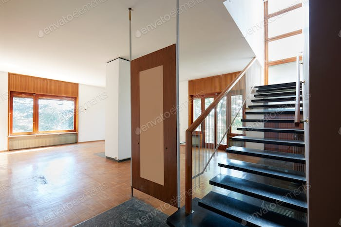 Empty living room with black marble staircase, apartment interior