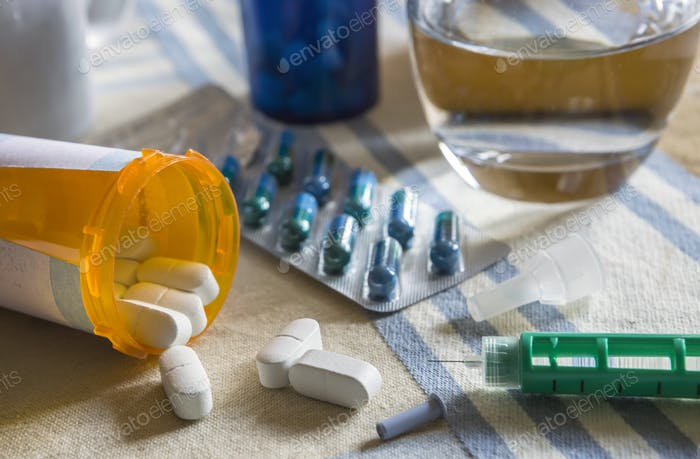 Medikamente während des Frühstücks, Kapseln neben einem Glas Wasser