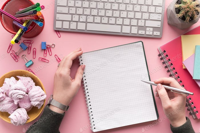 Frauen-Hände schreiben in Spiralblock