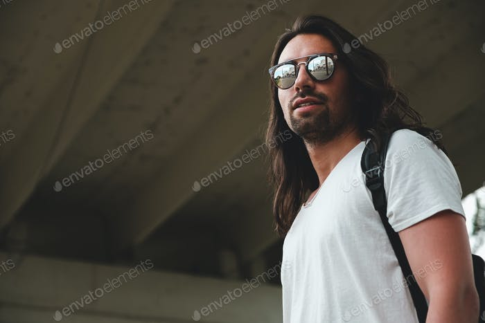 Model wearing fashionable sunglasses reflecting the city