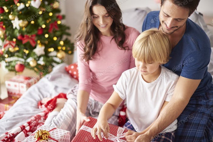 Family opening Christmas presents in the bed