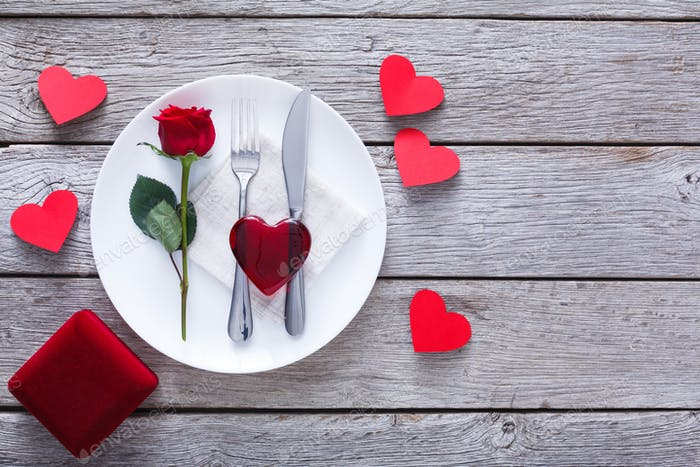 Engagement proposal background, cutlery, rose and glass heart on plate