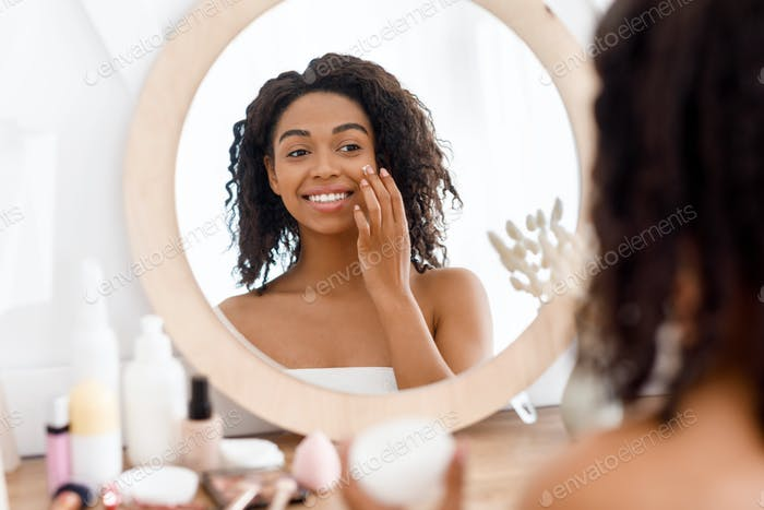 Pretty black woman looking in the mirror and applying facial moisturizer creme