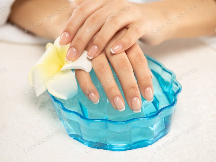 Woman gets manicure procedure in a spa salon. Beautiful female hands.