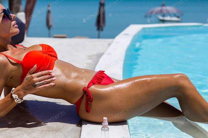 caucasian woman bronze shiny skin in bikini with coconut oil by blue swimming pool